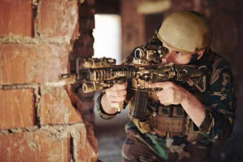 Soldier passing brick wall, weapon ready - Michal Dadson Counsels Veterans for PTSD and more