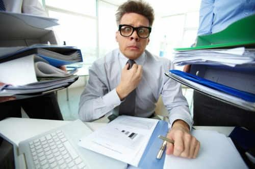 Man in office surrounded by disorganized papers – guilt and shame at work can lead to mental health issues