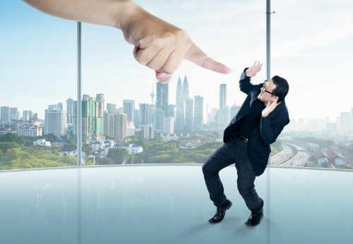 Giant finger pointing at guilty, ashamed executive in office with city view